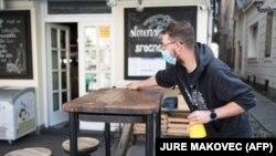 Egy csapos maszkban fertőtleníti az egyik asztalt egy ljubljanai kávézó teraszán 2020. május 4-én