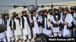 Taliban spokesman Zabiullah Mujahid (center, with shawl) speaks to the media at the airport in Kabul on August 31.
