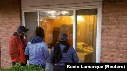 Члени сім'ї спостерігають за пацієнткою з коронавірусною хворобою з вікна медичного центру Аннандейла, штат Вірджинія, США, 27 квітня 2020 року