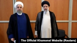 Former Iranian President Hassan Rohani (left) stands with Iran's new president, Ebrahim Raisi, during Raisi's inauguration ceremony in Tehran on August 3.