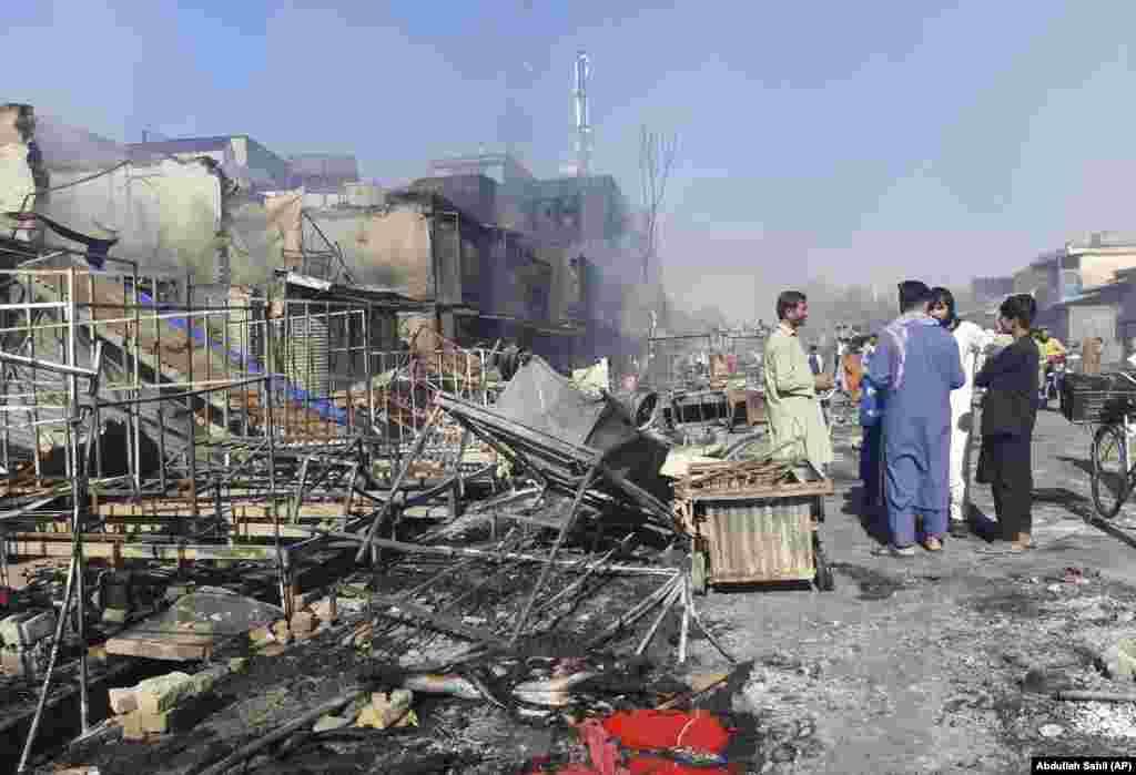 Авганистанци ги проверуваат оштетените продавници во северниот град Кундуз по судирите меѓу талибанските борци и авганистанските безбедносни сили на 8 август. Со околу 375.000 жители, Кундуз ќе биде најзначајниот град под контрола на Талибанците кои започнаа сеопфатна офанзива во мај како САД припадниците на силите ги започнаа последните фази од нивното повлекување.