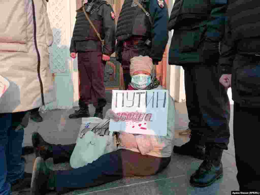 """A woman holds a poster reading """"Putin is a murderer"""" during the rally in Omsk."""