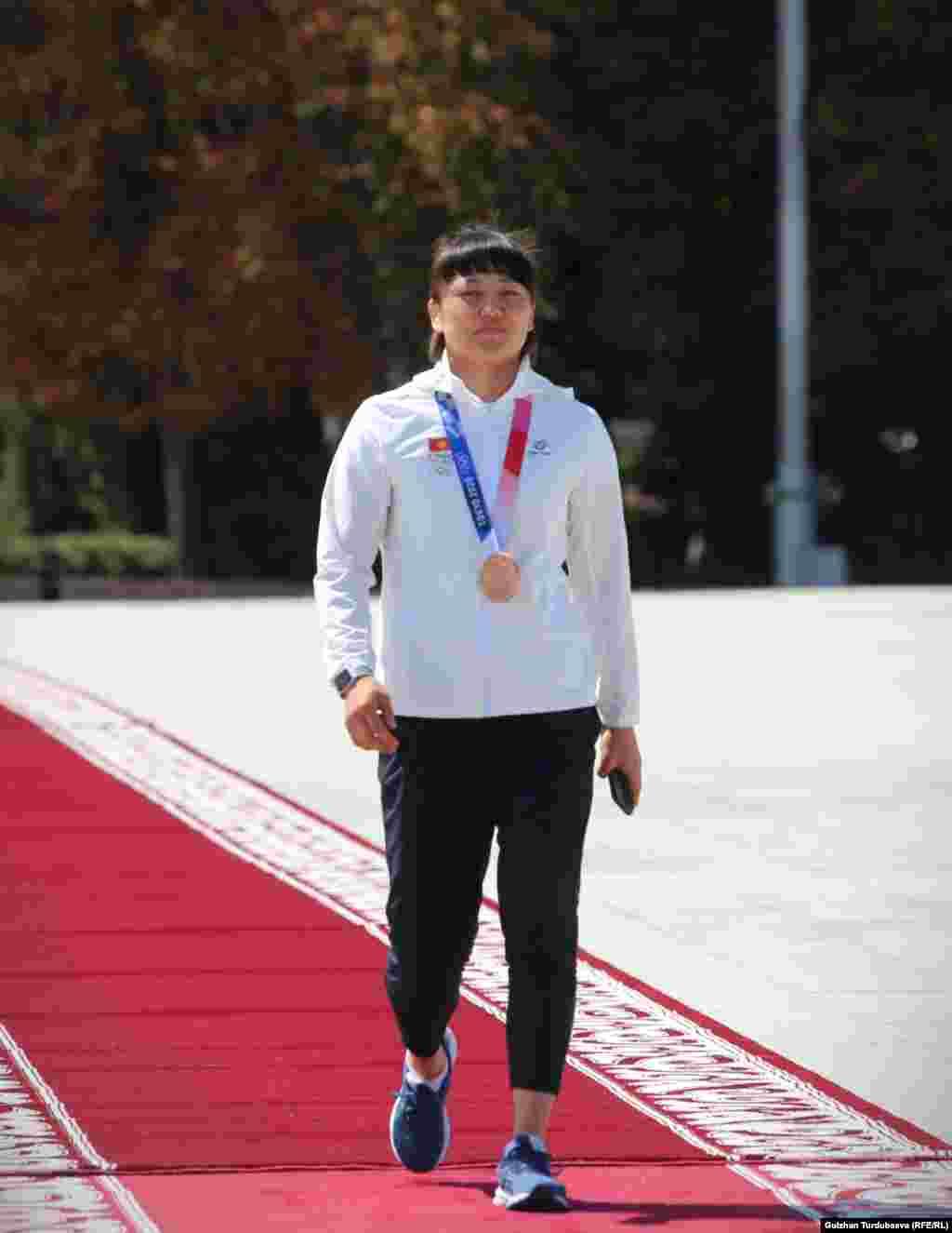 Токио Олимп оюндарында кыз-келиндер күрөшүнөн коло байге уткан Мээрим Жуманазарова эл алдына чыгып келет жатат.
