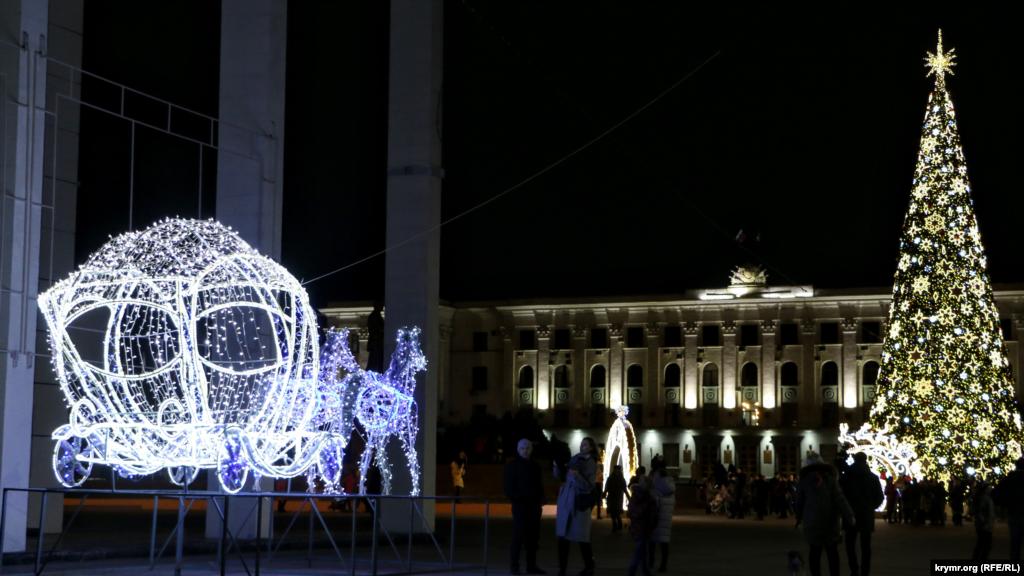 У Сімферополі запалили новорічну ялинку на площі Леніна. Неподалік встановили світлову інсталяцію у вигляді карети, запряженої кіньми