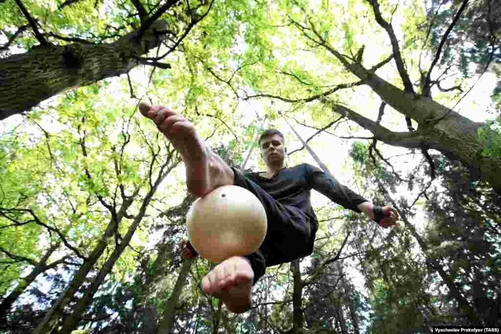 Антон Міхееў, акрабат з Маскоўскага цырку на Цьвятным бульвары, трэніруецца ў лесе ва ўмовах абмежаванняў з прычыны каранавірусу. (Dimitar Dilkoff/AFP)
