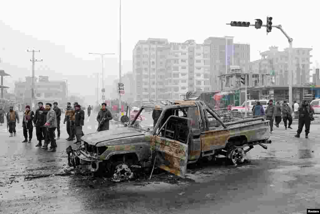 Afghan policemen inspect the site of a deadly car bombing in Kabul on December 20. (Reuters/Mohammad Ismail)