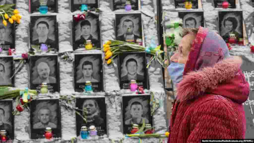 """Egy nő áll a """"Mennyei százaknak"""" elnevezettemlékmű előtt Kijevben február 18-án, hogy tiszteletét rója le a 104 ember emléke előtt, akiket a 2014-es kormányellenes tüntetéseken lőttek le."""