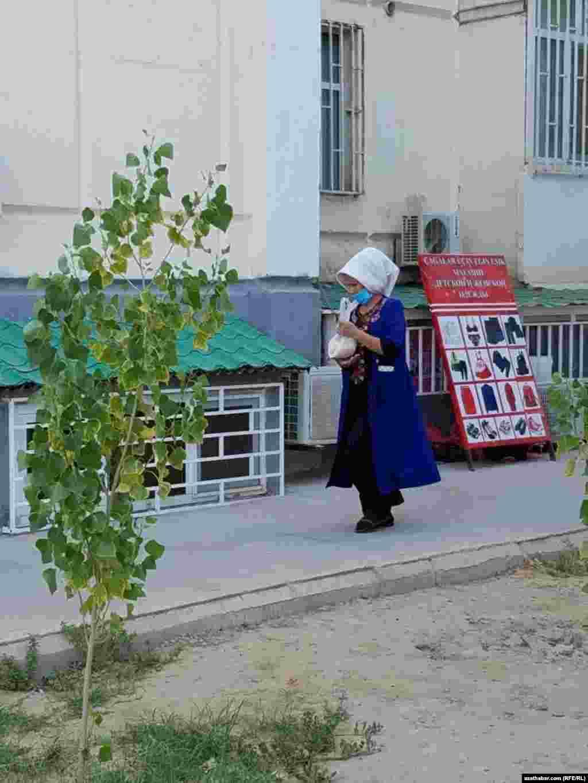 Aşgabat. Turkmenistan. COVID-19-dan goranmak we onuň ýaýramagynyň öňüni almak üçin ýüz maskasyny geýen zenan. 2021.