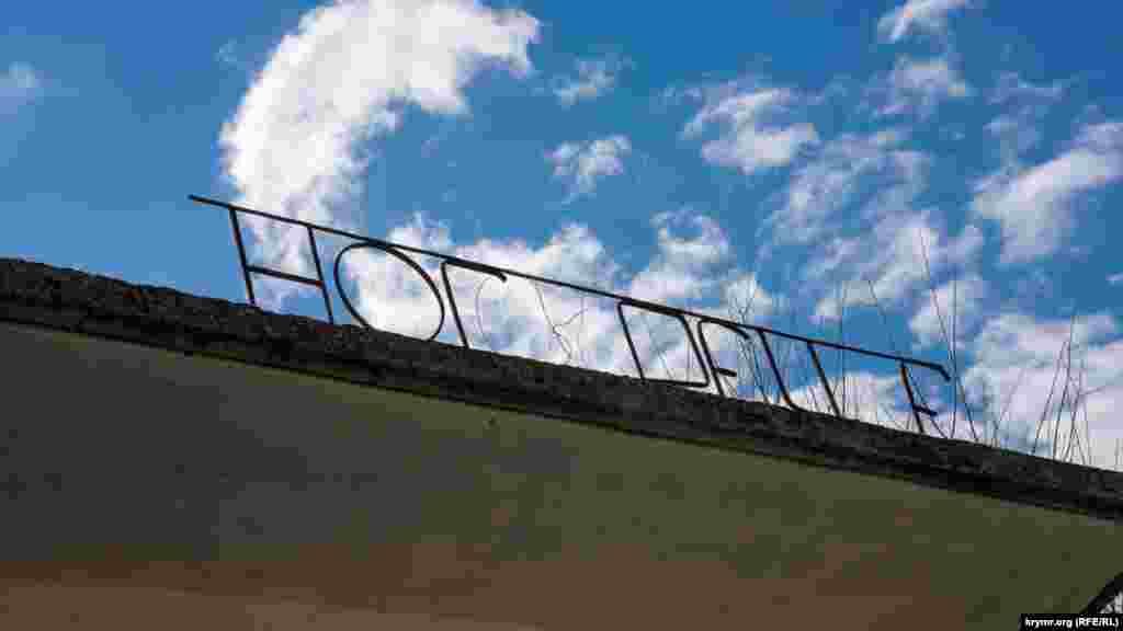 На крыше автобусной остановки сохранились не все буквы. Однако рейсовые автобусы из Бахчисарая давно сюда не ходят, а только до Счастливого, откуда до Многоречья полтора километра