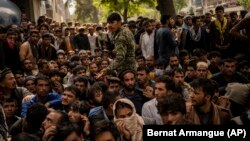 Afghans outside a bank as they try to withdraw money in Kabul on September 12.
