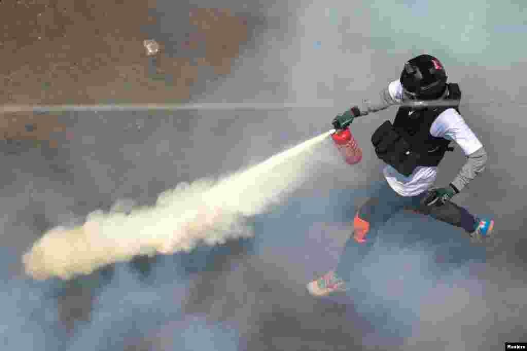 Бир демонстрант көздөн жаш агызчу газга каршы өрт өчүргүч затты чачууда. Янгон шаары, Бирма. 2021-жылдын 28-февралы.