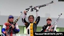 Ян Цянь из Китая празднует победу на пьедестале почета между россиянкой Анастасией Галашиной (слева) и Ниной Кристен из Швейцарии после победы в финале женской 10-метровой пневматической винтовки во время Олимпийских игр 2020 года в Токио. 24 июля 2021 года.