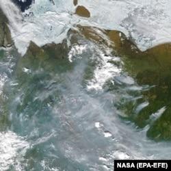 A satellite image shows smoke from active fires burning near Verkhoyansk on June 23