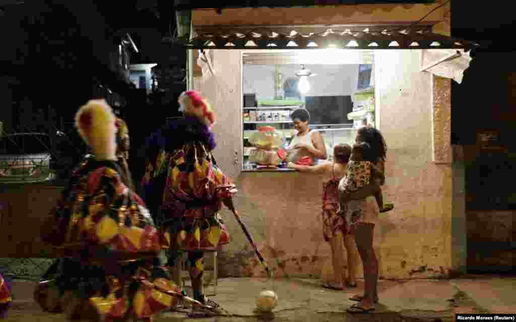 Попри те, що офіційно святкування карнавалу в Бразилії скасоване через пандемію COVID-19, ці двоє гуляк все одно вийшли на вулиці передмістя Ріо-де-Жанейро пограти з м'ячем