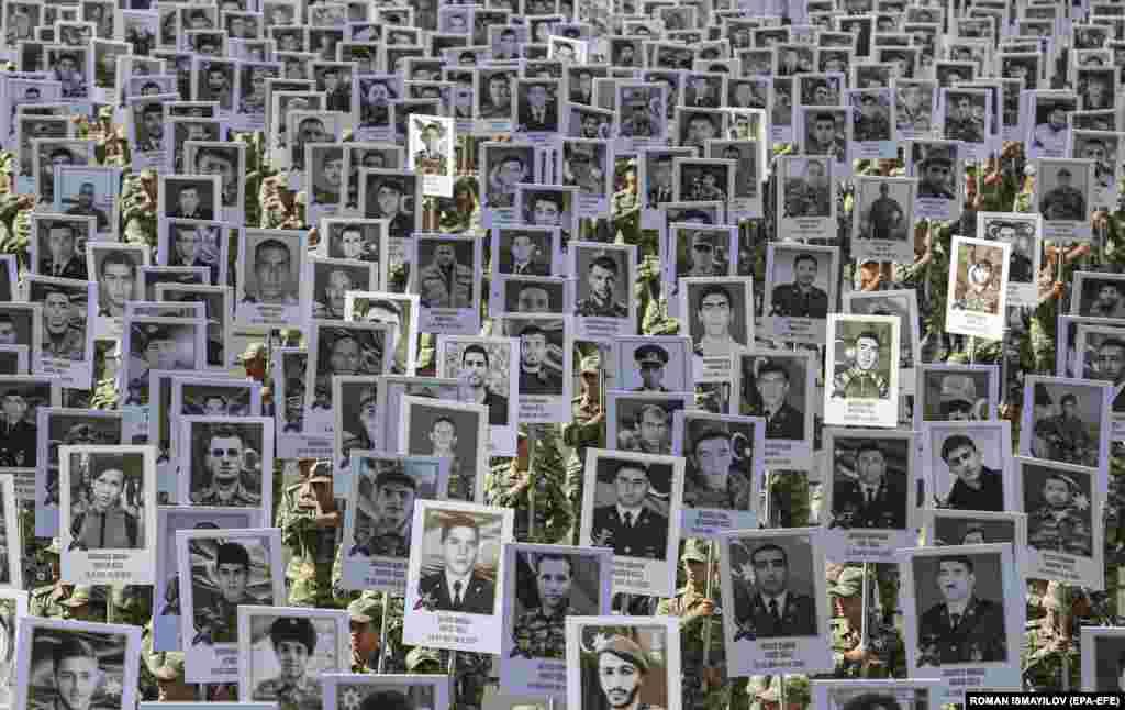 Soldați azeri poartă fotografii cu portretele militarilor și civililor uciși în timpul războiului de 44 de zile din Nagorno-Karabakh, din 2020, la marșul comemorativ organizat în centrul orașului Baku, Azerbaidjan.