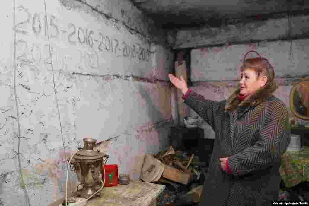 Женщина показывает даты, написанные на стене бомбоубежища в Ясиноватой. Среди них — Новый год, который жители отмечали в бомбоубежище.