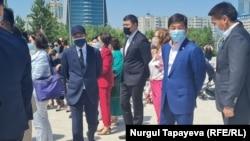 Первый заместитель председателя партии «Нур Отан» Бауыржан Байбек (второй справа) на церемонии открытия детской площадки. Нур-Султан, 27 мая 2021 года.