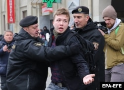 Police officers detain Raman Pratasevich as he attempts to cover a rally in Minsk in March 2017.