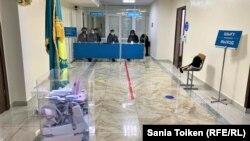Наблюдатели за стеклянной перегородкой на избирательном участке № 318 в городе Нур-Султане. 10 января 2021 года.