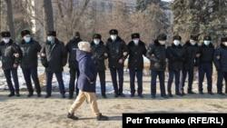 Шеп құрып тұрған полиция қызметкерлерінің алдынан өтіп жбара жатқан адам. Алматы, 10 қаңтар 2021 жыл.