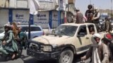 Victorious Taliban fighters drive an Afghan National Army vehicle through the streets of Laghman Province.