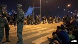 Ushtarët francezë bëjnë roje derisa shtetasit francezë dhe afganë presin të hipin në një aeroplan transporti ushtarak në aeroportin e Kabulit më 17 gusht 2021.
