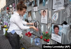 A volunteer dusts off portraits of St. Petersburg's medical workers who died from the coronavirus at an unofficial memorial in front of the local health department. The youngest worker honored there is 30-year-old nurse's aide Maria Tyshko.