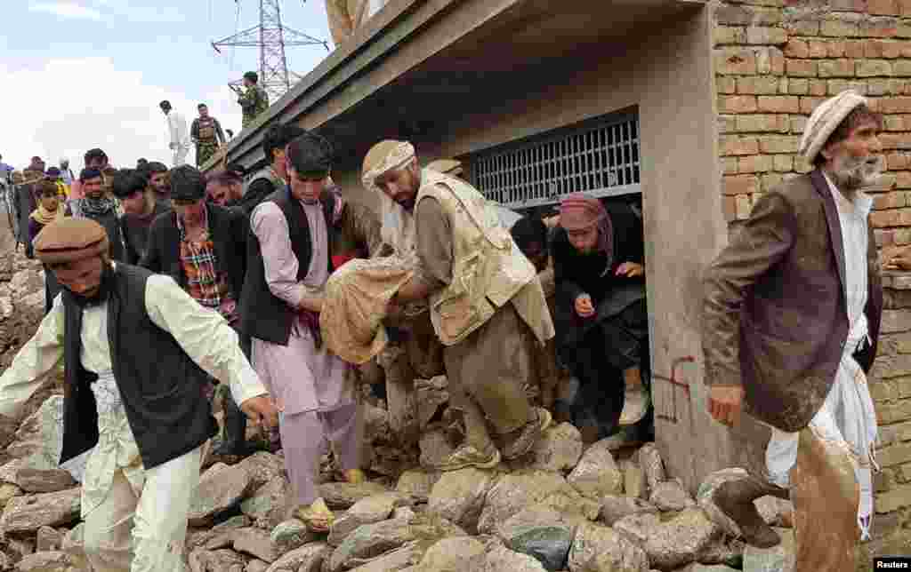 Men carry an injured person out of a house on August 26 after floods hit Charikar, the capital of Parwan Province.