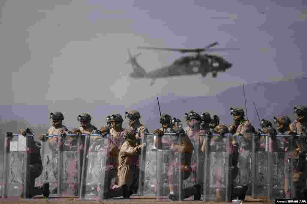 Ushtarët britanikë të NATO-s duke bërë ushtrime, teksa prapa tyre qëndronte në ajër një helikopter.