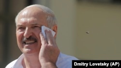 Belarusian President Alyaksandr Lukashenka wipes his face as he addresses supporters on Independent Square in Minsk on August 16.
