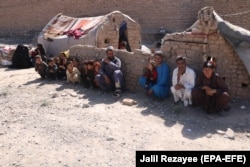 An internally displaced Afghan family outside a temporary shelter as they wait for relief from the authorities on the outskirts of Herat on June 15.