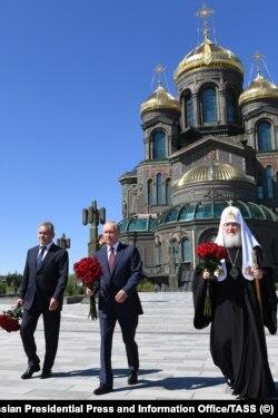 Szergej Sojgu védelmi minisztert gyakran emlegetik Putyin potenciális utódjaként. Ezen a képen az elnök és Kirill moszkvai és összorosz pátriárka társaságában látni a fegyveres erők fő temploma, a Feltámadott Krisztus-székesegyháznál