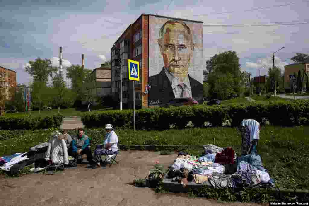 Уличные торговцы продают одежду и цветы возле многоквартирного дома с фреской с изображением президента России Владимира Путина в городе Кашира Московской области