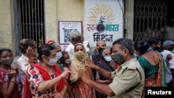 A police officer asks women seeking a dose of a COVID-19 vaccine to wait in line outside a vaccination center in Ahmedabad, India.