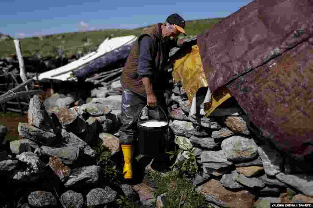 Bajram carries sheep's milk from his mountain hut.