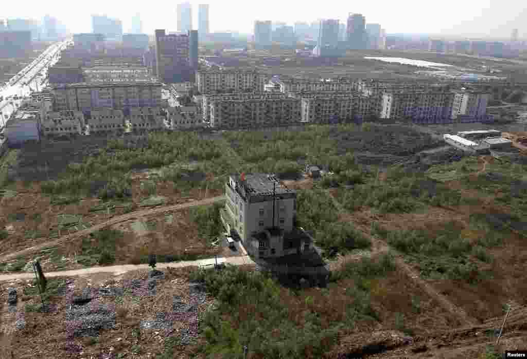 """""""Клинец"""" куќа сред градилиште за нова зона станбени згради во Хефеи, источна кинеска провинција Анхуи. Фотографирано на 5 ноември, 2007 година."""