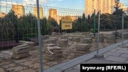 За строительным забором уже начались работы по демонтажу старых пешеходных плит