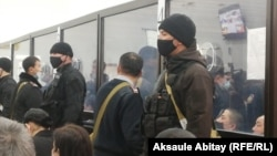 Defendants in the case are seen behind glass in the court in Taraz in December 2020 .