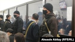 Defendants are seen behind glass in court in Taraz on December 3.