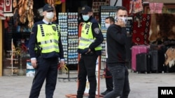 Илустрација- полиција и граѓани со заштитни маски во Скопје