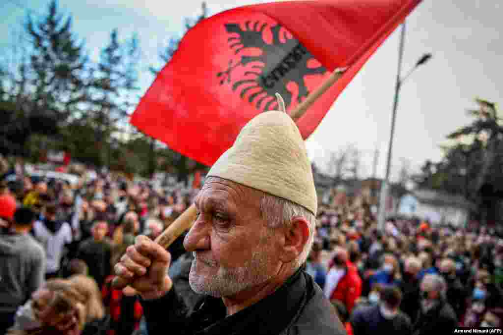 A supporter of the Vetevendosje (Self-Determination) movement waves an Albanian flag during an election rally in the town of Gjakova, Kosovo, on February 7. (AFP/Armend Nimani)