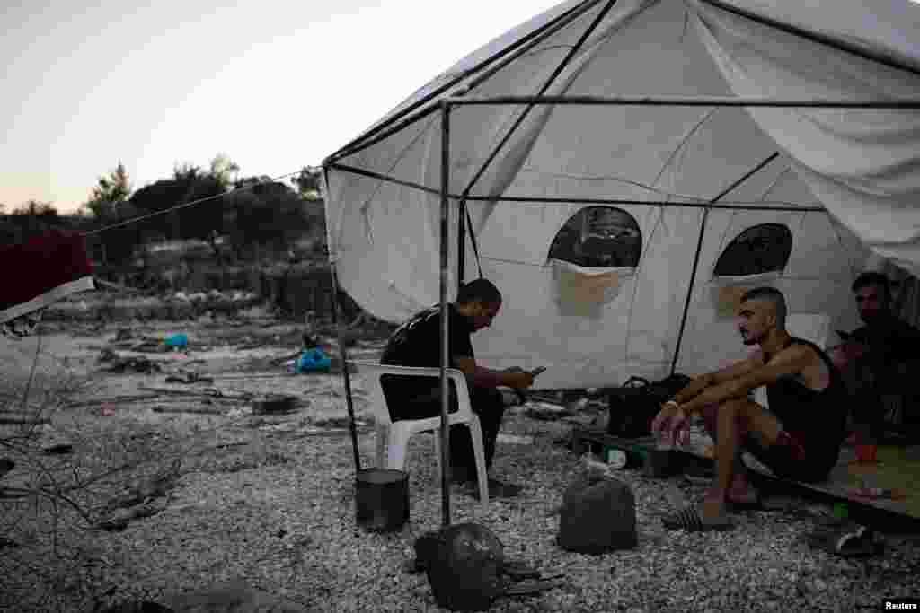 Migrantët e ulur nën një strehë të improvizuar pranë çadrave të djegura në kampin e shkatërruar Moria.