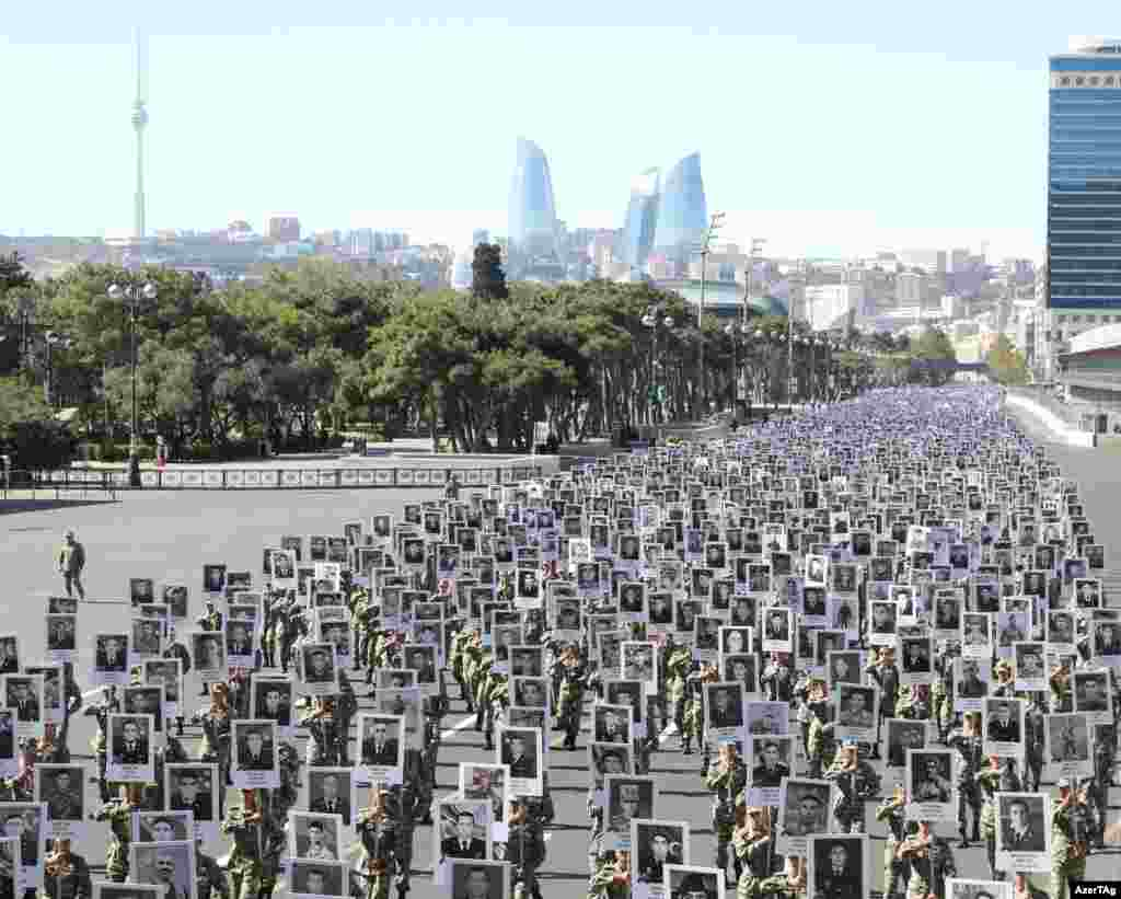 """Thousands of soldiers march through Baku on September 27. The marchers are holding placards depicting soldiers and civilians killed in 2020, the most intense escalation since the 1994 truce that turned the war between Armenia and Azerbaijan over the Nagorno-Karabakh region into a """"frozen conflict."""""""