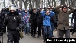 Őrizetbe vett tüntetőket kísérnek a rendőrök egy Alekszej Navalnij bebörtönzése ellen szervezett büntetés után Szentpéterváron, Oroszországban, 2021. január 31-én.