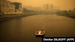 Vízibiciklizik egy pár Jakutszkban, 2021. július 27-én. A szibériai várost a környező erdőtüzek füstje borítja be