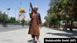 A Taliban fighter poses for a photo as he patrols in the city of Ghazni.