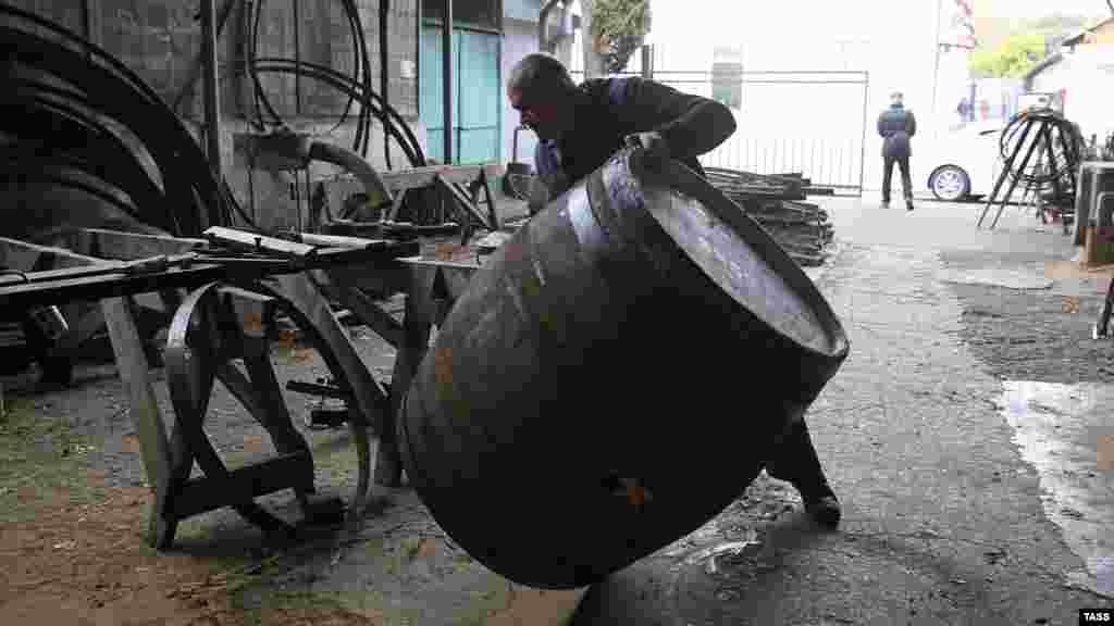 Мужчина переворачивает бочку на территории винзавода