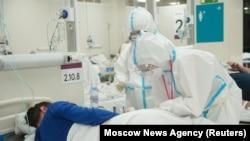 Медработники и пациент в автоцентре, переоборудованном под временную больницу. Москва, 30 октября 2020 года.