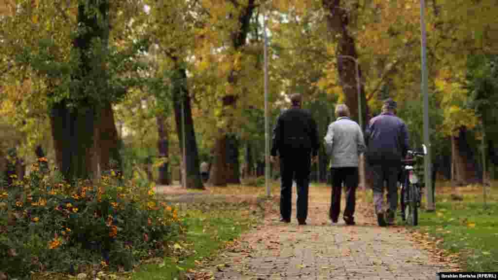 Tre të moshuar ecin në parkun brenda qytetit, në Tauk Bahçe.