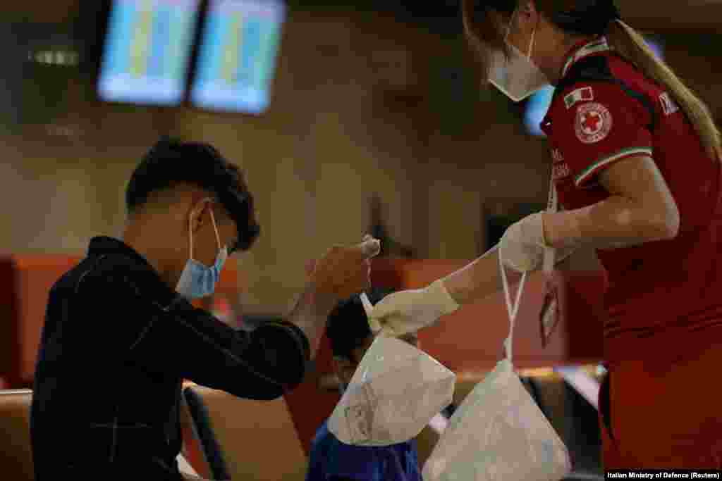 Афганский мальчик получает сумку с едой от работника Красного Креста после приземления рейса из Кабула в Риме 16 августа